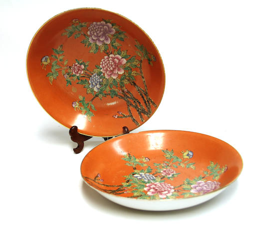 A pair of coral ground porcelain deep dishes with famille rose enamel decoration Qianlong marks