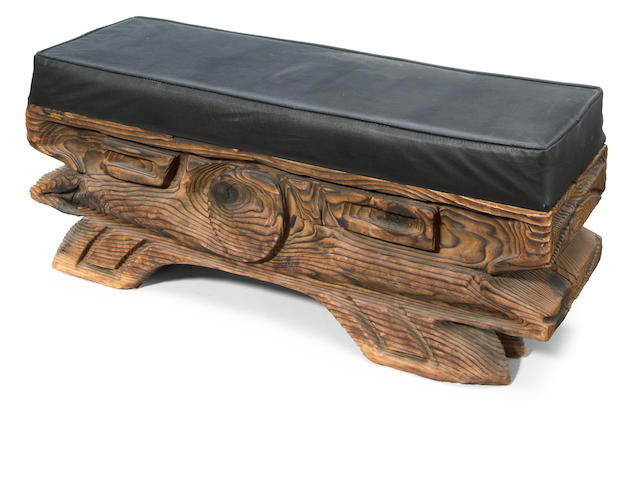An upholstered carved wood low bench