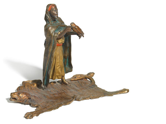 A Franz Bergman cold painted bronze figure of an Arab merchant on tiger skin rug  circa 1900