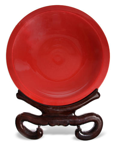 A Chinese sang de boeuf glazed porcelain charger on ebonized hardwood  stand