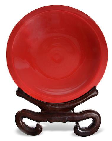 A Chinese sang de boeuf glazed porcelain charger on ebonized hardwood  stand