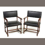 A pair of Continental Baroque style walnut and leather armchairs