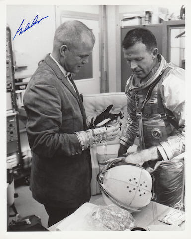 GLENN INSPECTING COOPER'S SPACE SUIT. Black and white photograph,
