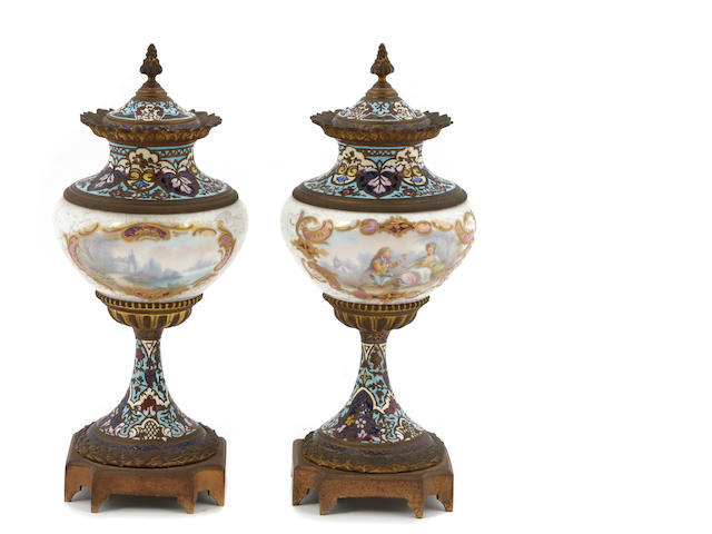A pair of French porcelain, gilt bronze and champlevé covered urns