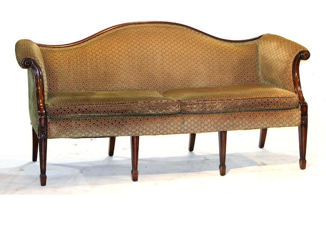 A pair of George III style camel back sofas