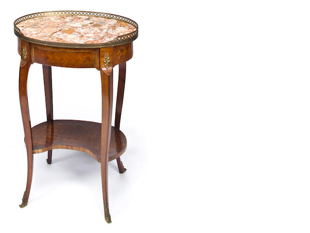 A Louis XV/XVI Transitional style gilt bronze mounted mahogany and satinwood gueridon with brown-beige marble top<BR />late 19th century