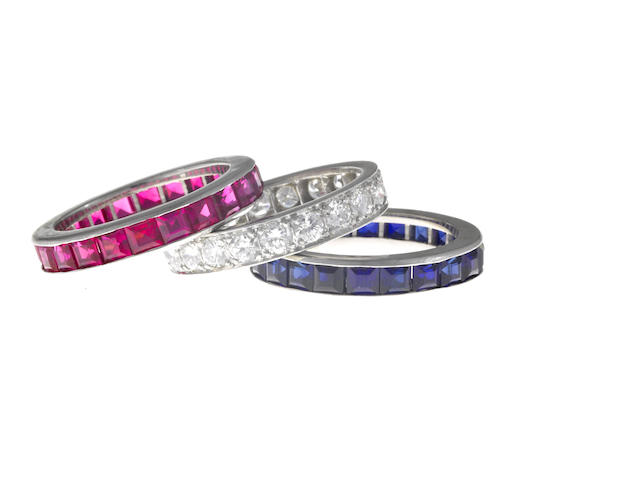 A diamond and platinum eternity band together with two synthetic ruby, synthetic sapphire and fourteen karat white gold rings