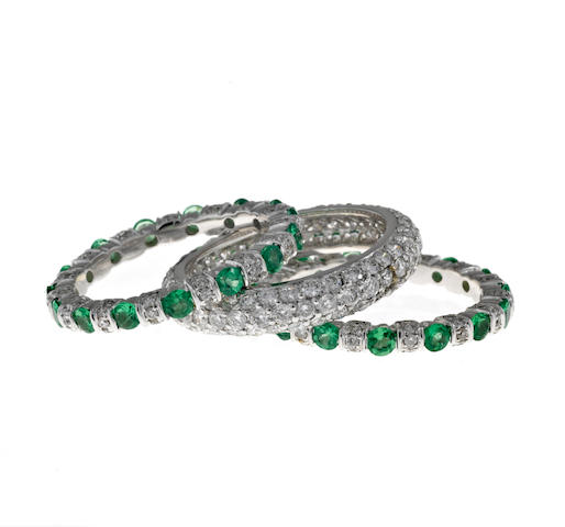 A diamond pavé eternity band together with two tsavorite garnet and diamond eternity bands