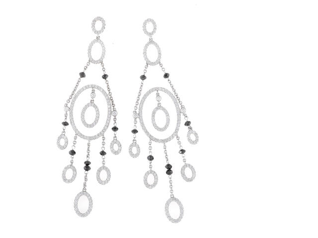 A pair of diamond and black diamond chandelier earrings
