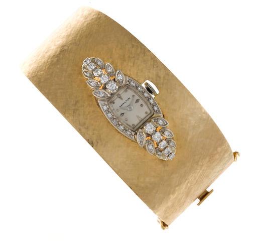 A diamond and fourteen karat white gold wristwatch, Hamilton, in a fourteen karat yellow gold bangle bracelet