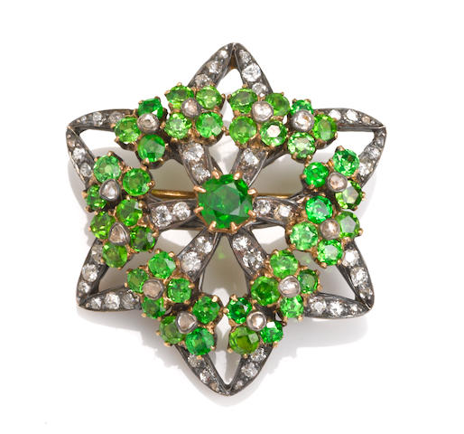 A demantoid garnet and diamond stylized flower motif brooch