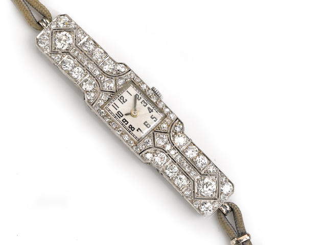 A diamond and platinum wristwatch with fourteen karat white gold and cord strap