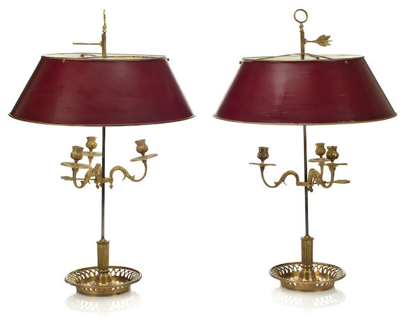 A pair of Louis XVI style gilt bronze and steel bouillotte lamps with red tole shades