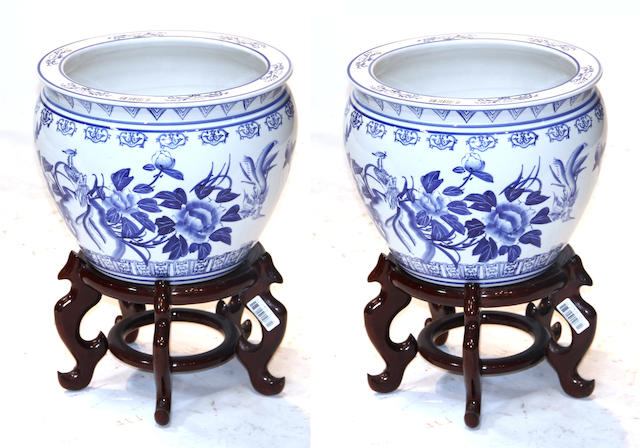 A pair of Chinese blue and white fish bowls on stand