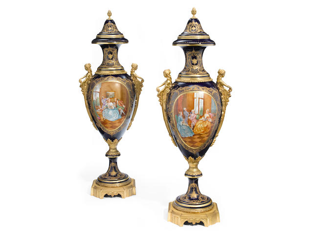 An imposing pair of Sèvres style gilt bronze mounted porcelain urns