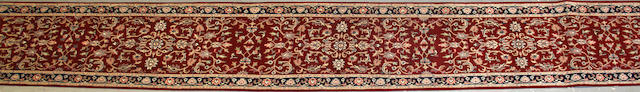 An Indian carpet size approximately 2ft. 6in. x 20ft. 4in.