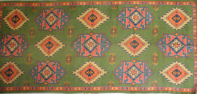 An Arts & Crafts long carpet size approximately 6ft. 8in. x 14ft. 4in.