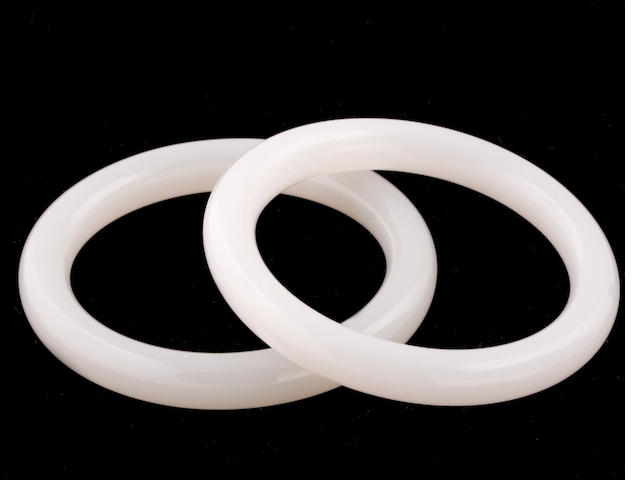 A pair of two white jade bangles