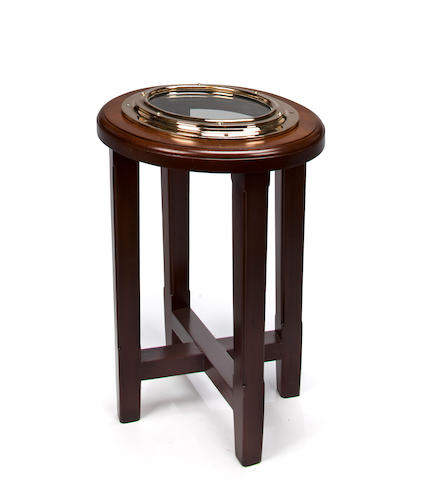 A small oval end table with an inset catboat porthole  22 x 17 in. (55.8 x 43.1 cm.) height x width.