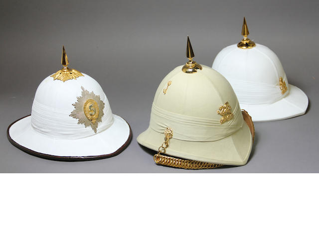 A lot of three pith helmets with British regimental insignia