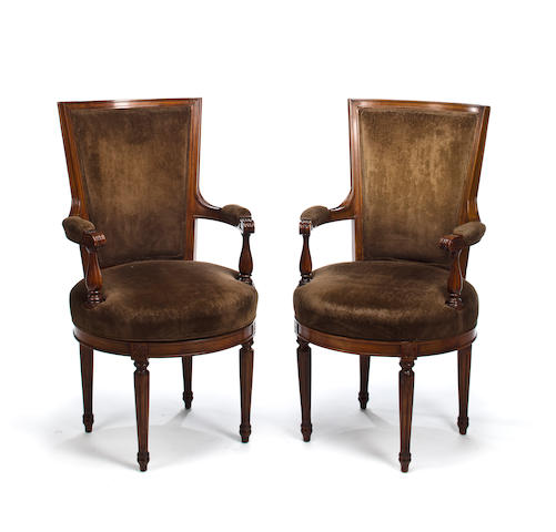 A pair of Louis XVI style walnut swivel armchairs<BR />20th century