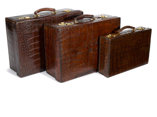 A Drew & Sons crocodile attaché case, Mawson, Swan & Morgan crocodile suitcase and another crocodile suitcase <BR />second quarter 20th century