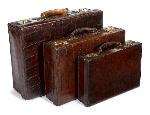 An Asprey crocodile attaché case and two crocodile suitcases