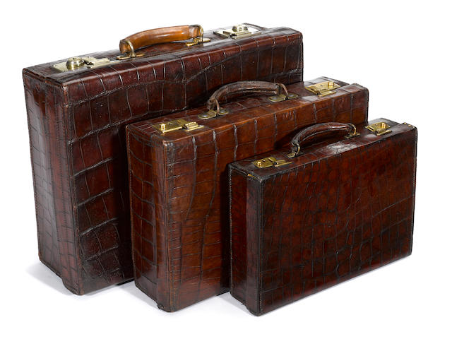 An Asprey crocodile attaché case and two crocodile suitcases<BR /> second quarter 20th century