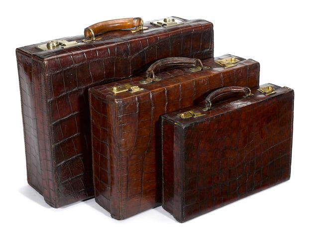An Asprey crocodile attaché case and two crocodile suitcases<BR /> second quarter 20th century