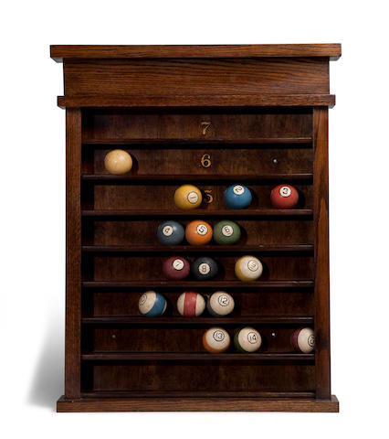A billiard ball wall rack and vintage ball set  29 x 23 in. (73.6 x 58.4 cm.) the shelf. 16