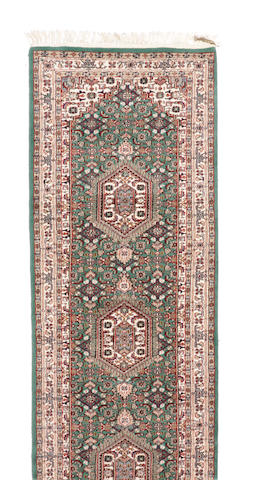 An Indian carpet size approximately 2ft. 6in. x 19ft. 5in.