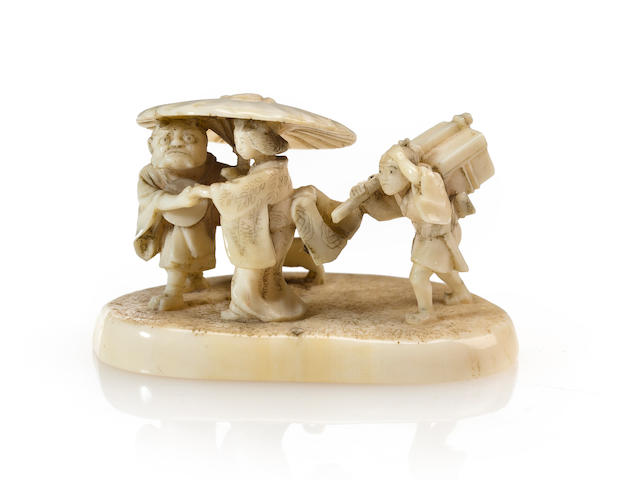 An ivory netsuke of a woman and oni
