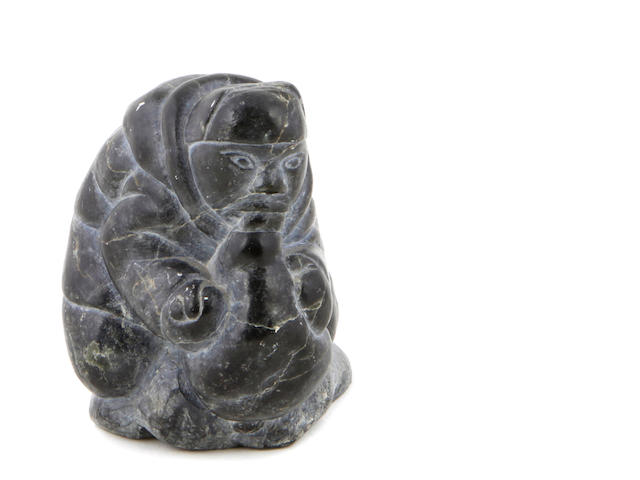 An Inuit carved soapstone figure of a crouching hunter