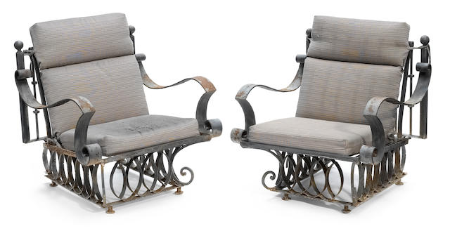 A pair of wrought iron garden armchairs