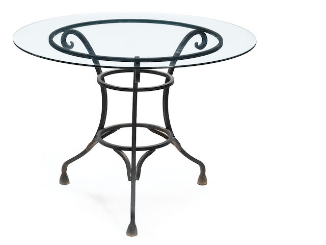 A Rococo style wrought iron and glass circular outdoor dining table