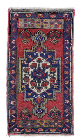 A Turkish rug size approximately 1ft. 7in. x 3ft. 5in.