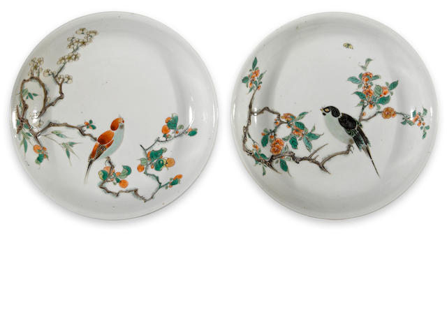 Two famille verte enameled porcelain deep dishes with flower and bird decoration Kangxi period One with green enameled bamboo, and the other with iron red bamboo on the exterior walls.  diameter 8 ¼in (both with restored hairline cracks)