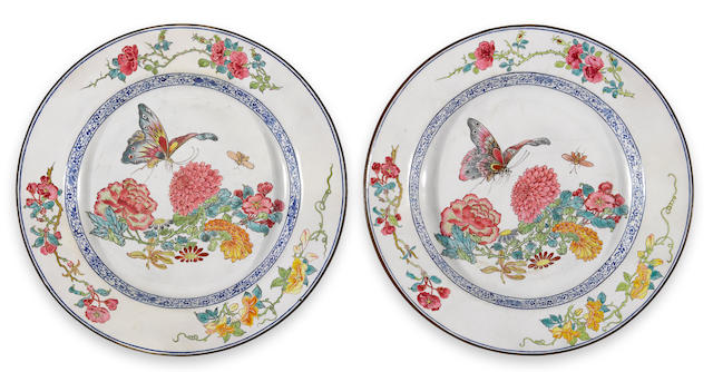 A pair of Canton enameled white ground metal dishes with butterfly and flower decoration Qianlong period diameter 8 ¾in (restoration to cavetto, hairline cracks, backs of both restored)