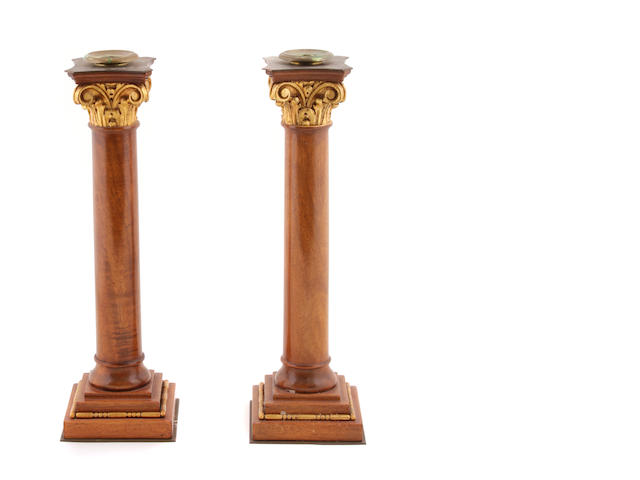 A pair of Neoclassical style parcel gilt mahogany candlesticks