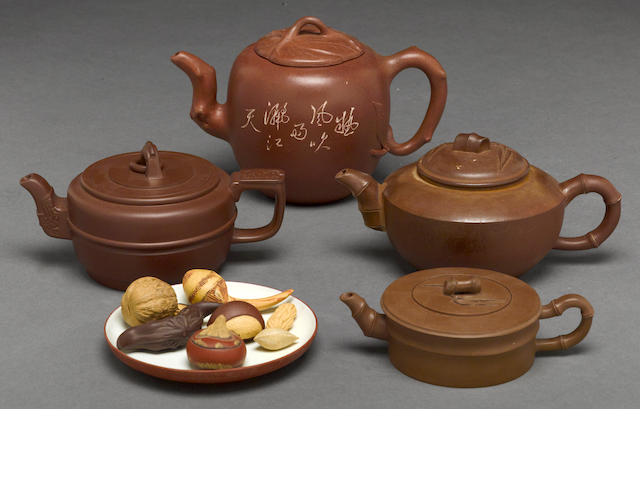 Four Yixing teapots, together with a tray and eight nuts and sweets