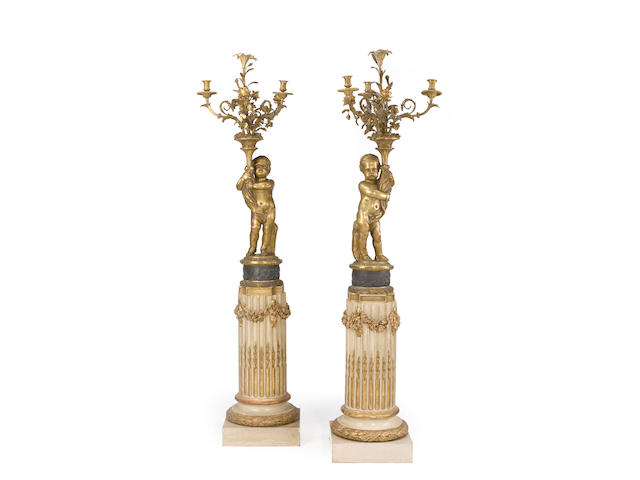 A pair of Louis XVI style gilt and patinated bronze x-light candelabras together with a pair of Louis XVI style painted and parcel gilt pedestals<BR />fourth quarter 19th century