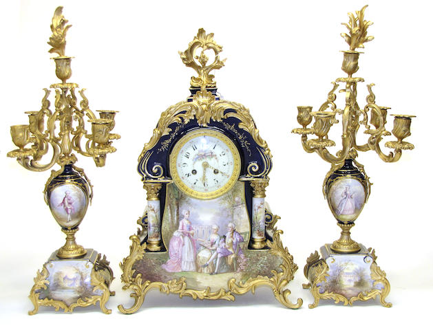 A Louis XV style gilt bronze mounted ceramic clock garniture retailed by J. E. Caldwell & Co., Philadelphia<BR />first quarter 20th century