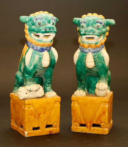 A pair of green ochre and straw glazed ceramic leonine beasts Late Qing/Republic period