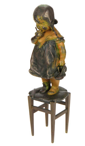 A spelter and bronze figure of a child standing on a stool
