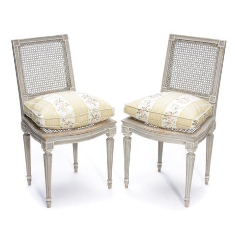 A pair of Louis XVI style paint decorated cane side chairs