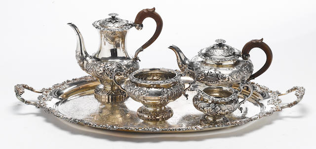 A George IV/William IV silver assembled and matching four piece tea and coffee set with wooden handles and with a modern plated tray G. Burrows II and R. Pierce, London, 1836 (pots)<BR />Joseph Angell, London, 1823 (cream pitcher and sugar bowl)  <BR />Rubenesque cherubs, with crest  (5)
