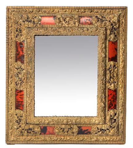 A Dutch Baroque style repoussé brass wall mirror