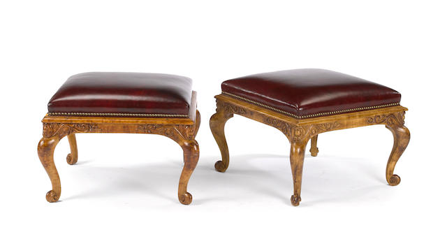 A pair of Rococo style fruitwood and leather stools<BR />20th century