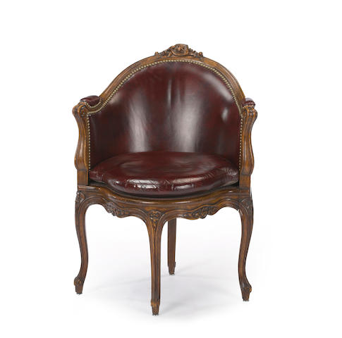 A Louis XV style beechwood, leather and cane upholstered bergere de bureau <BR />late 19th century