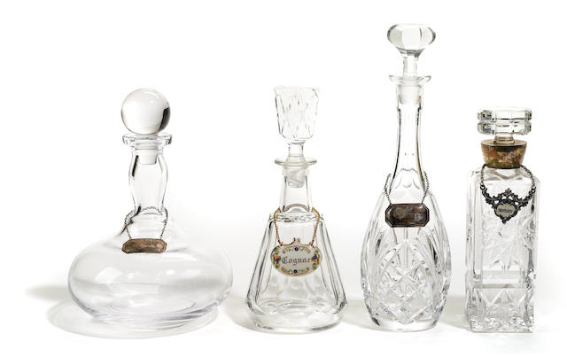 A group of ten cut glass decanters and stoppers with bottle labels